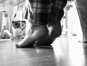 Photo from under the bed on barefoot woman in pajamas at morning